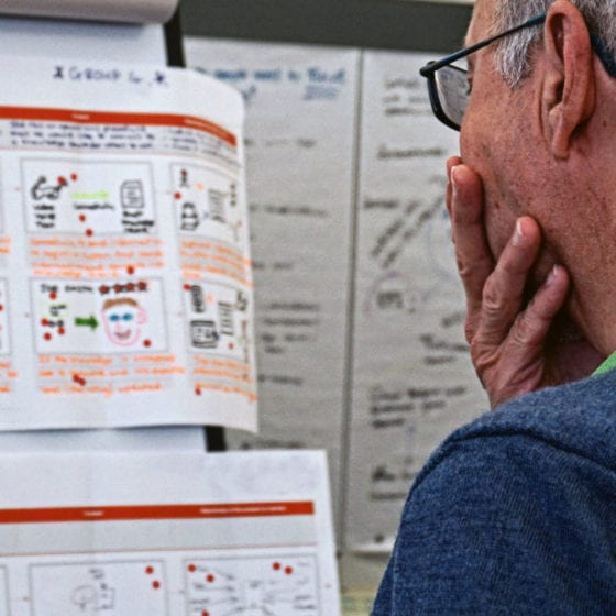 man looking at workshop outputs